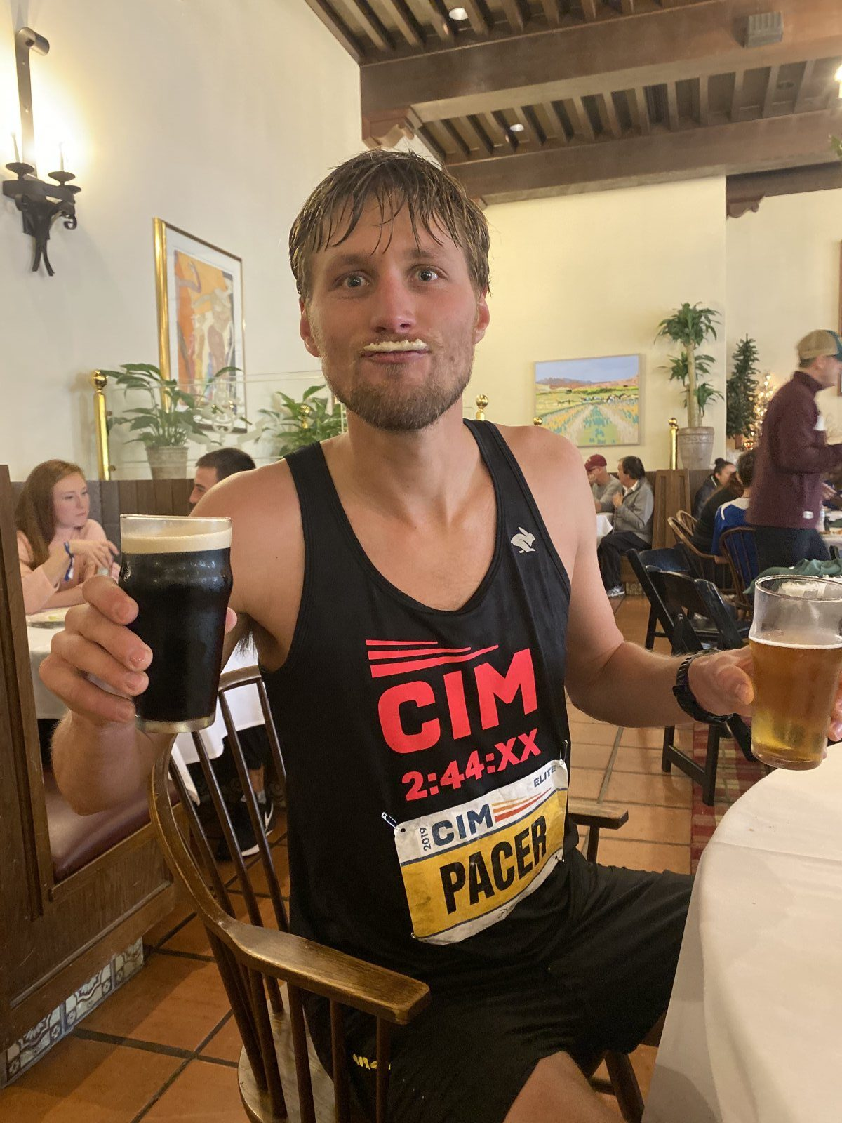 CIM pacer enjoying two beers with foam on his lip